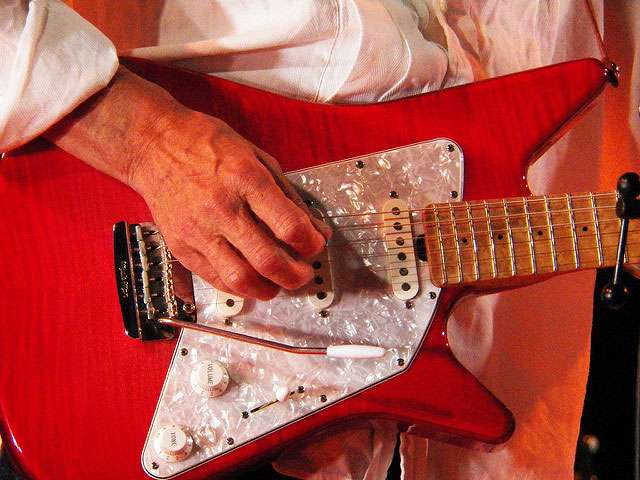 A detail of a man holding a bright red electric guitar.