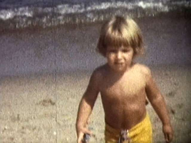 A boy with blonde hair walks along the beach in a vintage video clips.
