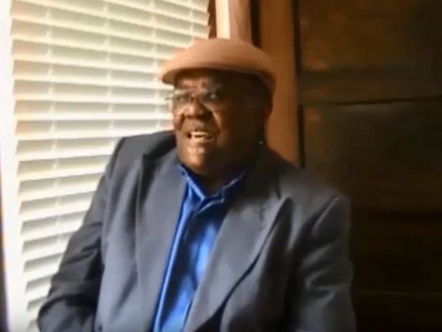 A man with a brown hat and a gray jacket sits in front of a window and talks to an interviewer