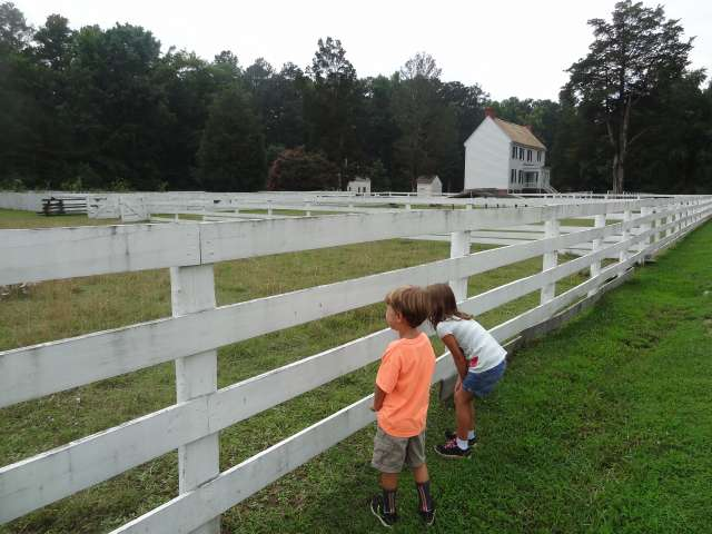 Children look through a fence in a small American town.