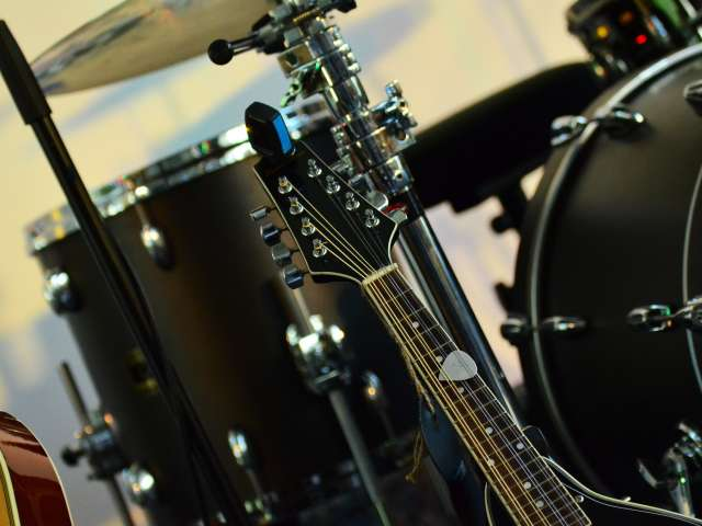Musical instruments such as drums and guitars on a stage.