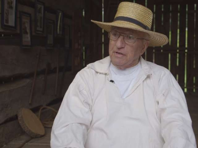 A man in 18th-century period clothing talks about the creation of the Hoff Barn.