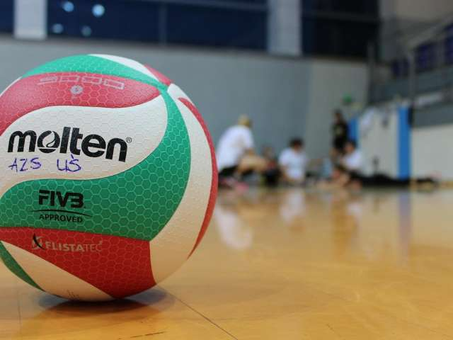 A red and green volleyball on a shiny court. Pixabay stock photo