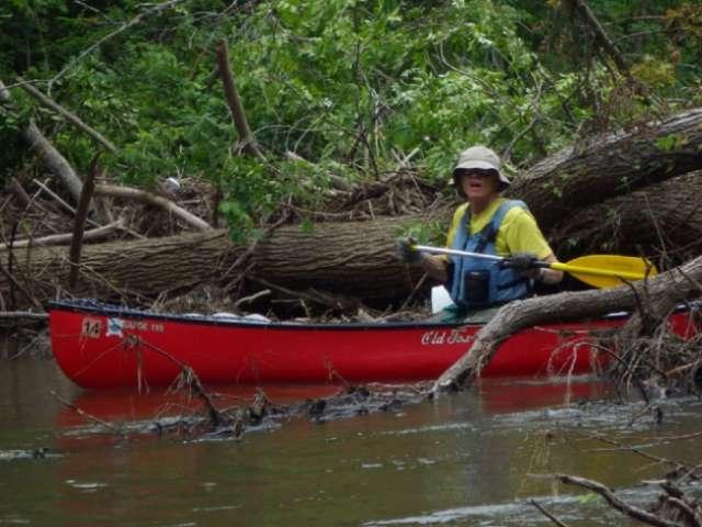 Mark Bosacker paddles in a red canoe.