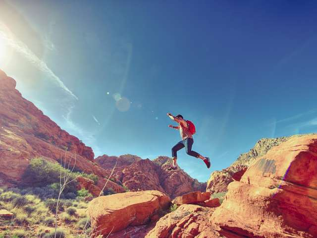 A person jumps across red rocks in a desert landscape.