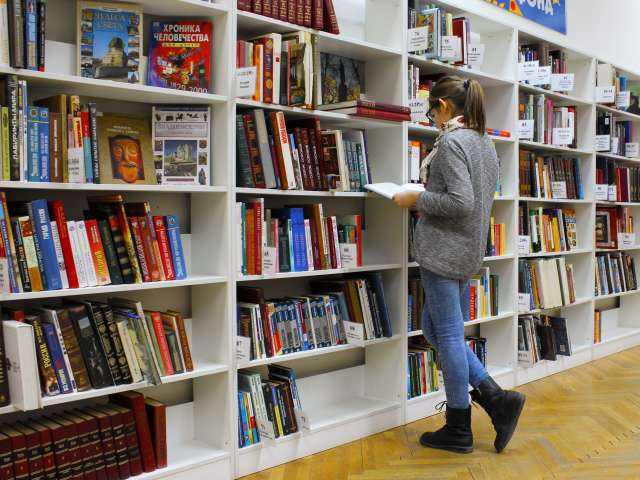 A girl looks through a books on a bookshelf at a library. Pexels stock photo