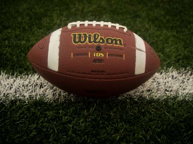 A Wilson football rests on the white line of an American football field. Pexels stock photo