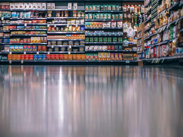 The interior of a grocery stores, showing canned goods stocked on shelves. Pexels stock photo