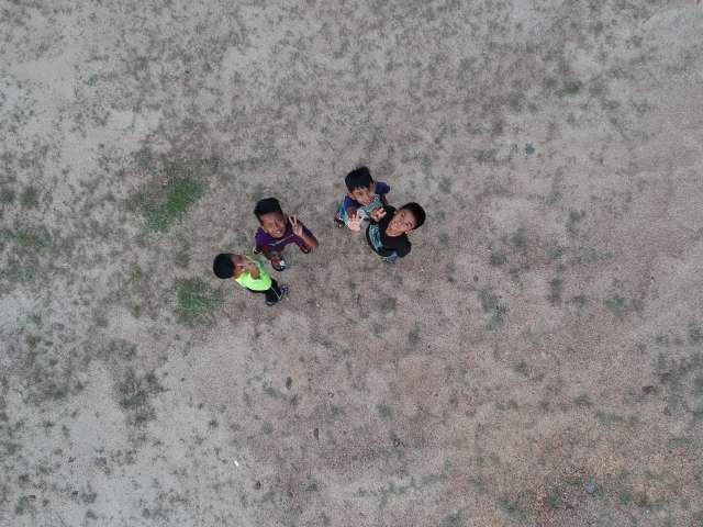 A group of small children making peace signs, as photographed from above. Pexels stock photo