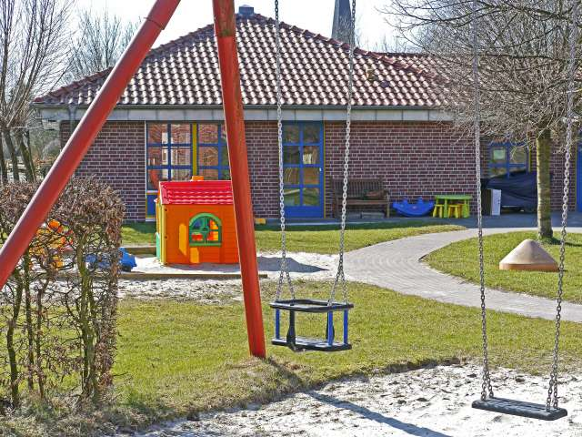 A playground with a plastic playset and swings. Pexels stock photo