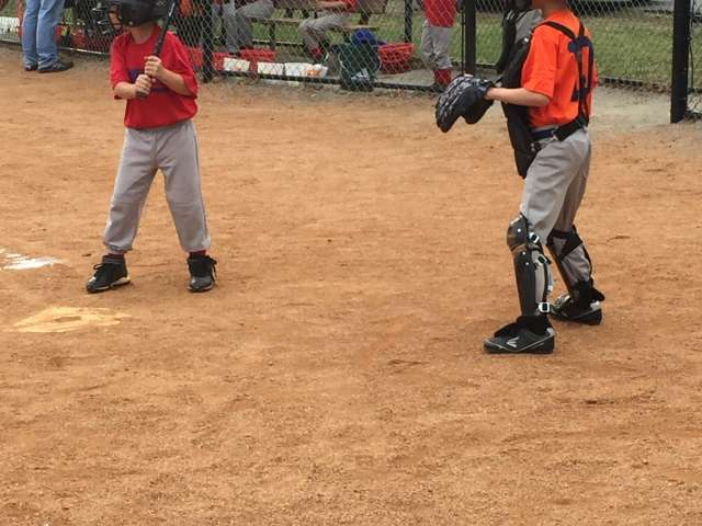 Two boys sport baseball gear in a Little League game. Photo by Heather Shelton