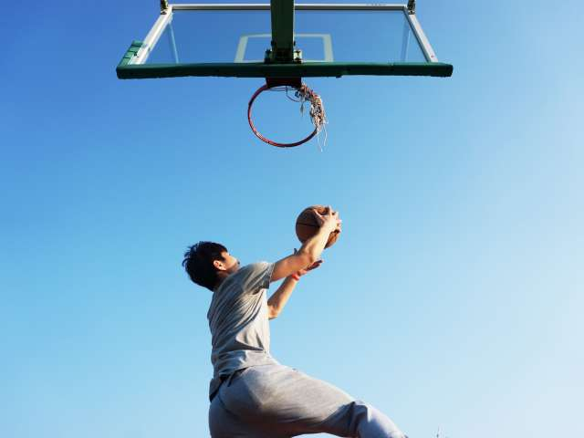 A boy jumps to make a lay up on a basketball court. Pexels stock photo
