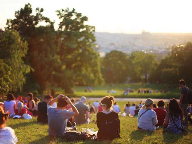 A group of youth sit on a hillside and listen to a concert. Pexels stock photo