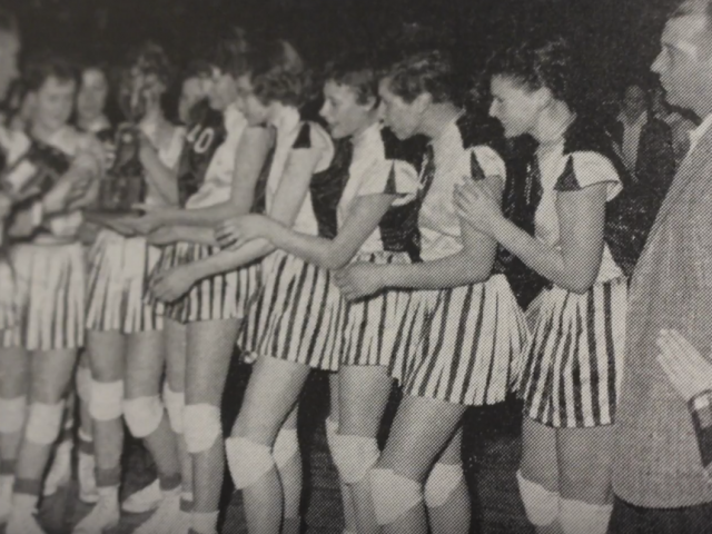 Vintage photo of women on the sidelines of a 6-on-6 basketball game, wearing striped shorts.