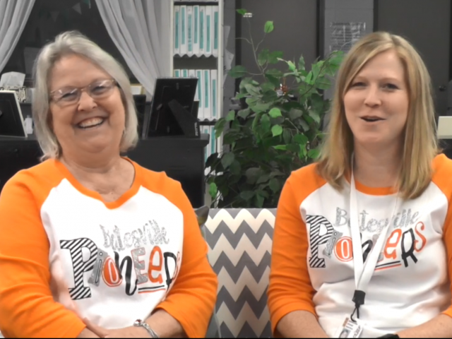 Two women, a mother and daughter, wear orange and white t-shirts and sit on a couch with gray, zigzag stripes.