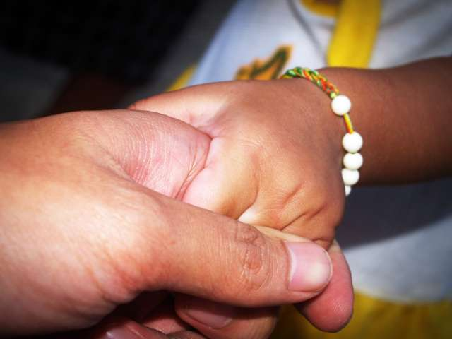 A detail of a person holding a child's hand. Pexels stock photo.