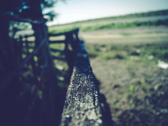 A blurred image of a vintage fence railing on a farm. Pexels stock photo.