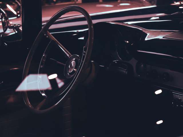 The interior of a vintage car showing its steering wheel. Pexels stock photo.