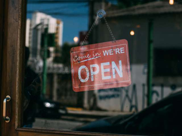 A photo of an open sign in a small-town store window. Pexels stock photo.