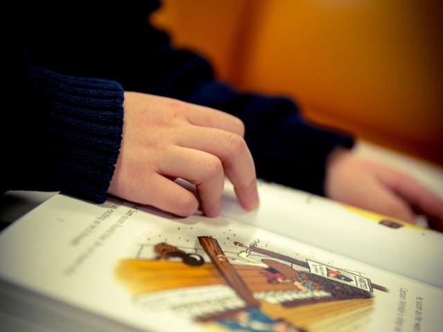 A detail of a child flipping through a picture book. Pexels stock photo.