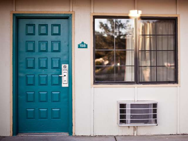 The blue-green entry door of a motel. Pexels stock photo