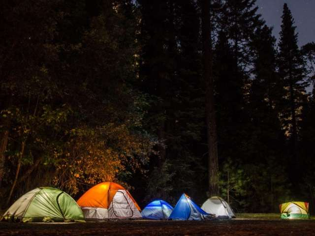 A nighttime view of a group of tents with lights inside them. Pexels stock photo